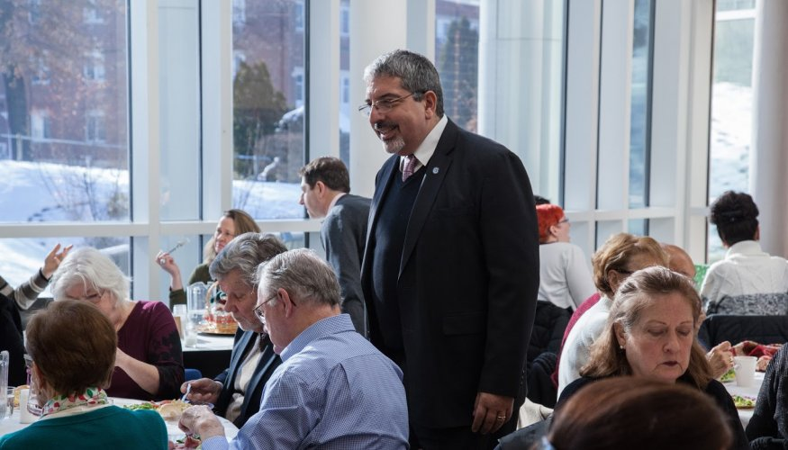 QCC President Dr. Luis Pedraja greets faculty and staff during the recent holiday luncheon.