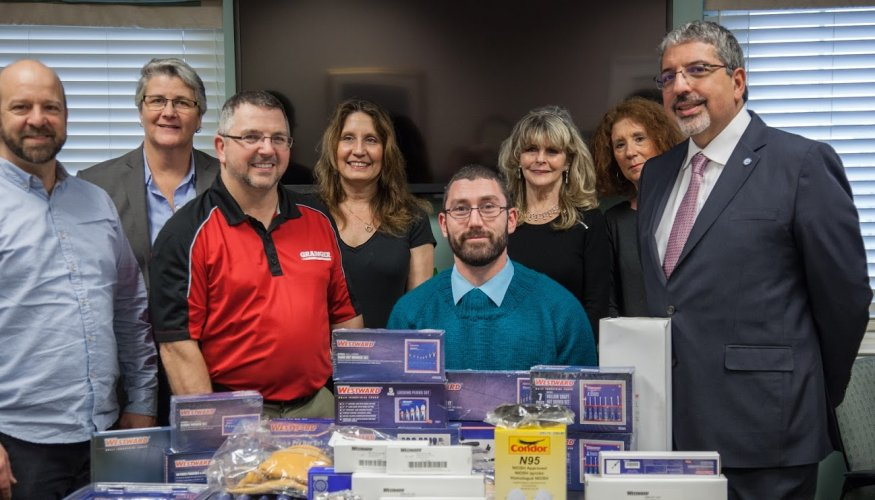 QCC Grainger Scholarship winner Jason Bulter (center) and Edward Weatherbee (Grainger) are surrounded by staff and faculty from QCC.