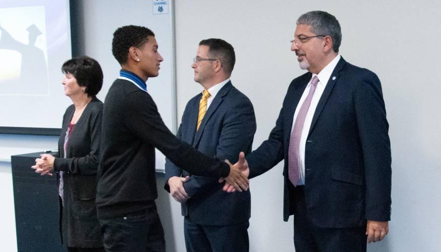 QCC President Dr. Luis Pedraja greets student Johathan Mora.