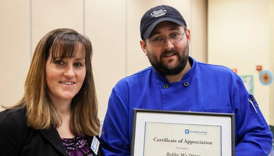 Nicole Wheeler awards a Certificate of Appreciation to Bobby M's Diner.