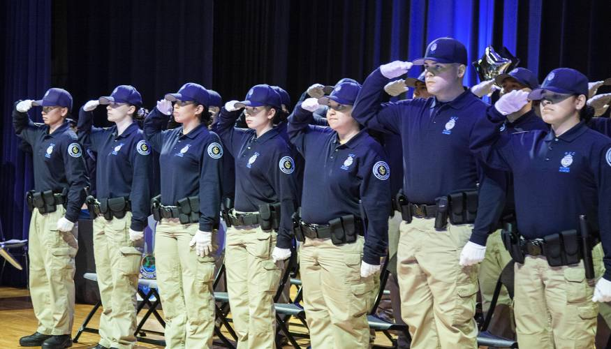 QCC's first graduating class from the college's police academy salute the American flag.