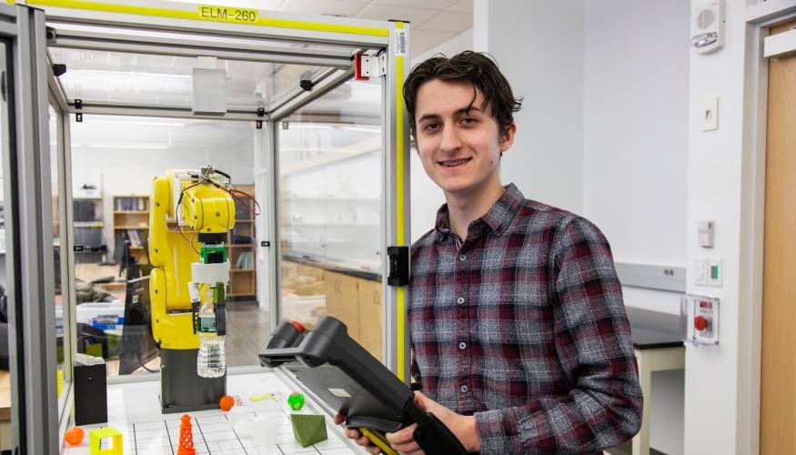 Hunter Boudreau programs the FANUC robot to pick up and move a water bottle.