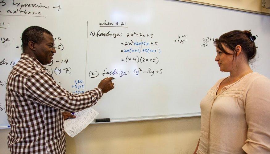 Associate Professor Sheiba Mas-Oud explains a mathematics problem to student Bethany Bailey.