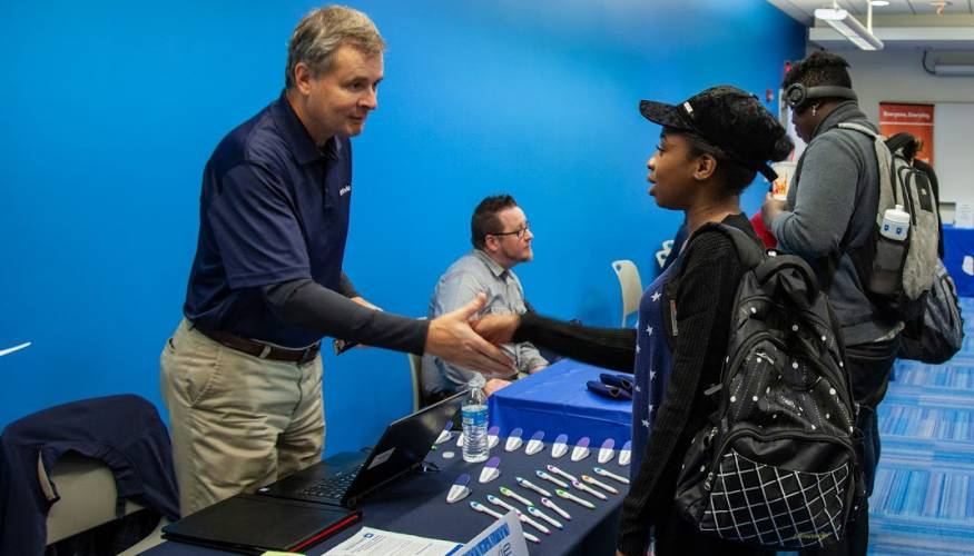 AbbVie Project Manager John Sauers greets a QCC student at the recent QCC Job Fair.