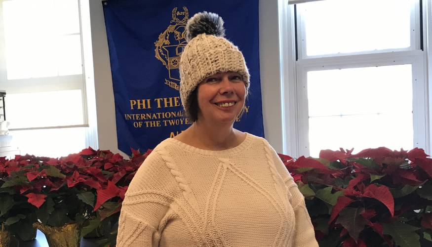 PTK Advisor Bonnie Coleman is surrounded by poinsettas PTK is selling to raise funds for the new Live and Learn Greenhouse.