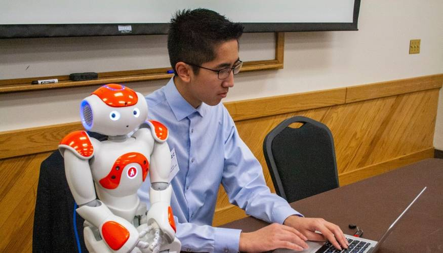 QCC student Anthony Le works on a computer program that will enable the robot to perform a function.