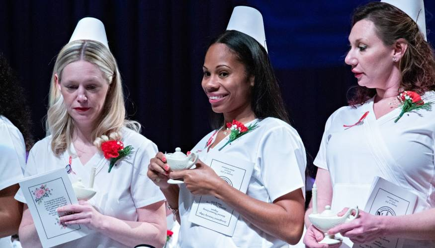 Nursing graduates from the evening program receive their lamps during a December pinning ceremony.