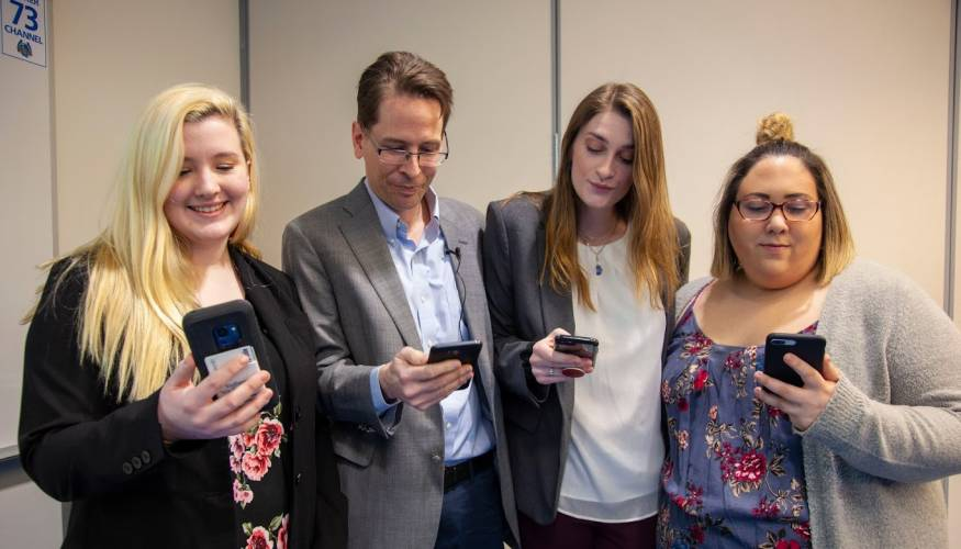 Dr. Peter Frost (center) discusses cell phone usage and its effects with students.