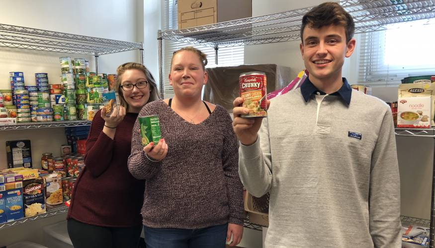 From left: PTK students and food pantry volunteers Emma O'Brien, Ashley Forhan and Max German in the new QCC Food Pantry