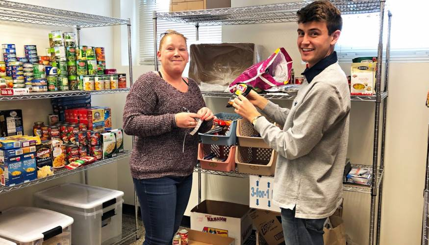 Outgoing Food Pantry Manager Ashley Forhan works with incoming Food Pantry Manager Max German.