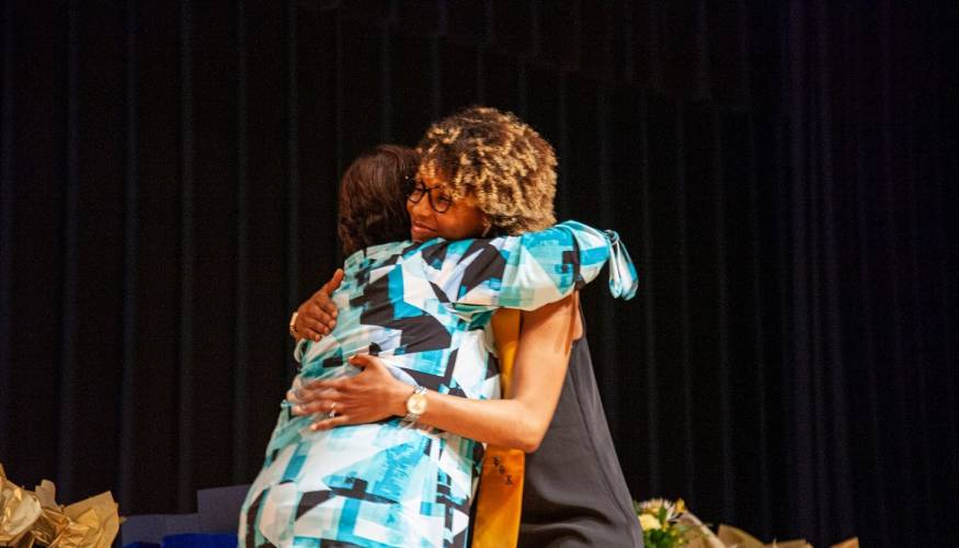 PTK Adviser Bonnie Coleman gives a hug to PTK graduate Gina Ilas.