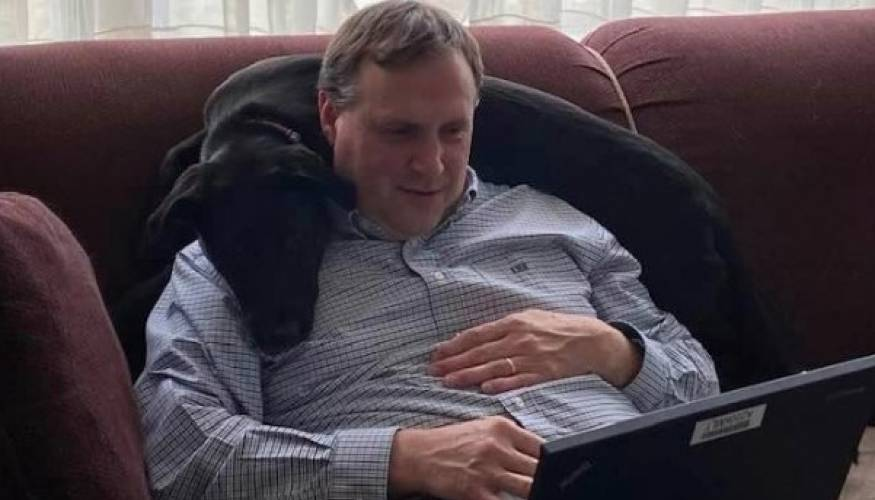 QCC's Assistant Director of Advancement Program and Services Keith McKittrick gets a helping hand (paw!) as he works remotely.