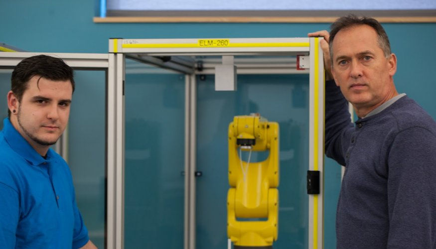 From left: QCC student Nick Voyer checks out a FANUC robot with Manufacturing Technology Professor, Damian Kiernan.