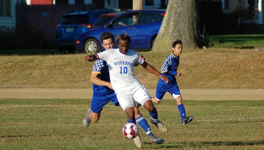 QCC soccer player Samuel Museme powers the ball forward.