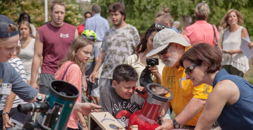 students view eclipse through telescopes