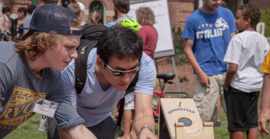 students view eclipse through telescopes