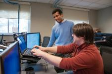 QCC instructor helps student with programming laptop